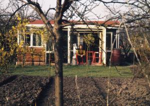 Jan Wolkers zit buiten voor zijn tuinhuis op Amstelglorie