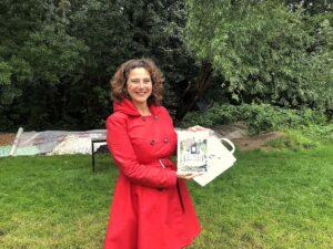 wethouder Marieke v Doorninck met boek Volkstuinverhalen op Amstelglorie